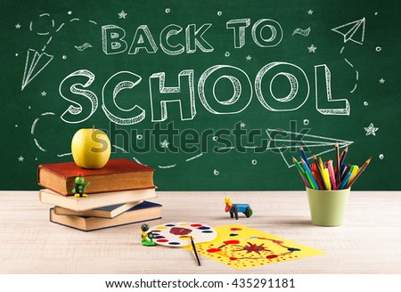 Back to school concepty with writing on blackboard and desk, apple, books, items - stock photo