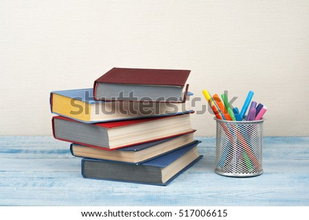 Back to School education concept with hardback books stacking and colorful pencils on wooden table and beige background.