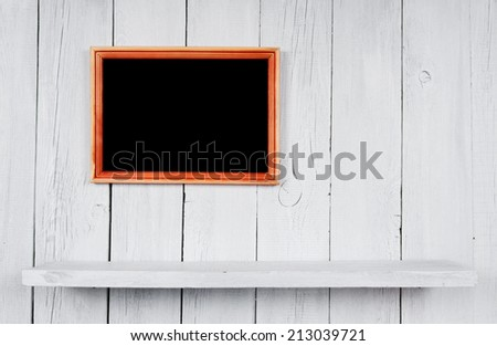 Back to school. Frame and a wooden shelf. A white, wooden background.