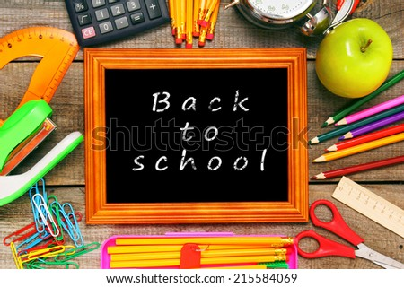 Back to school. Frame and school tools. Vertically. A wooden background. - stock photo
