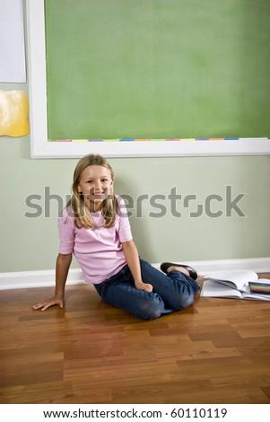 Back to school - girl in classroom by green blackboard, 8 years old - stock photo