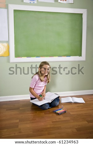 Back to school - girl writing in classroom by green blackboard, 8 years old