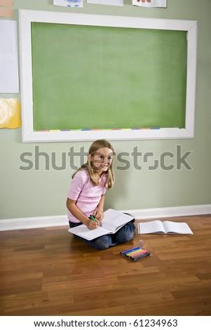 Back to school - girl writing in classroom by green blackboard, 8 years old - stock photo