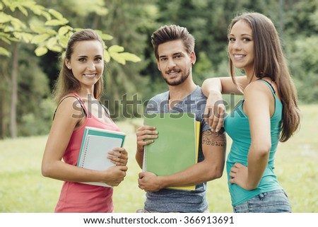Back to school, group of young students and friends posing at the park, they are holding notebooks and smiling at camera - stock photo