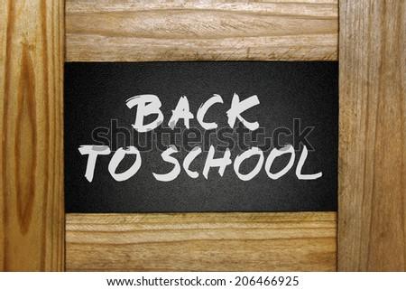 back to school handwritten on blackboard in wooden frame - stock photo