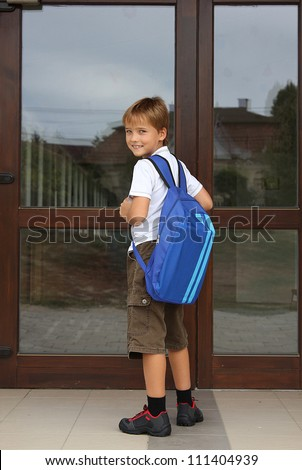 Back to school - happy young boy standing in front of the entrance of the school - school concept - stock photo