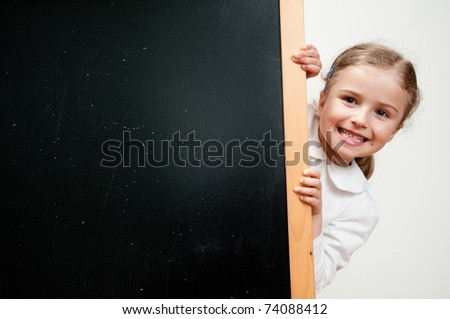 Back to school -little schoolgirl and blackboard - space for text - stock photo