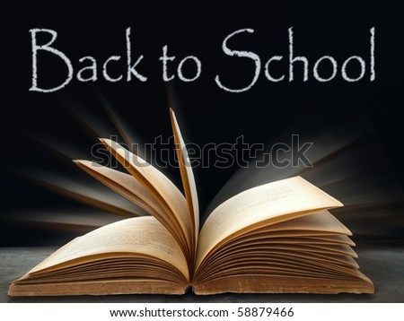 back to school on Black board and book on table