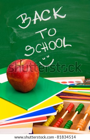 Back to school on chalkboard with school supplies - stock photo