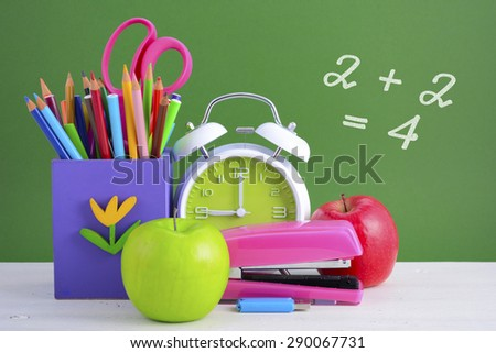 Back to School or Education Concept with classroom desk and bright colored stationery supplies on white wood rustic table and green board background.  - stock photo