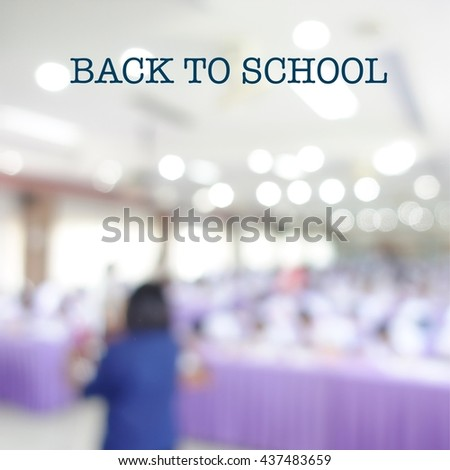 Back to School phase on blurred classroom with male teacher standing on front and male and female students sitting and listening for lecture - stock photo