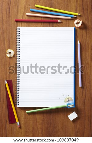 Back to School pupils art pencils and pad on wooden school desk from above - stock photo