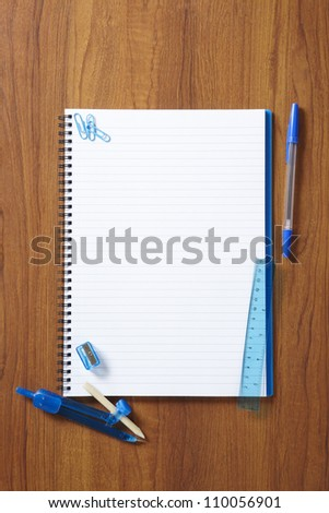 Back to School pupils note pad and stationary on wooden school desk from above - stock photo