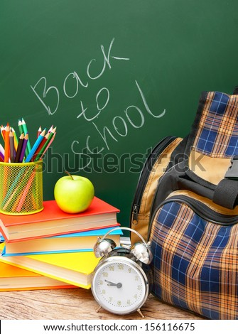 Back to school. School bag and school accessories against a school board. - stock photo