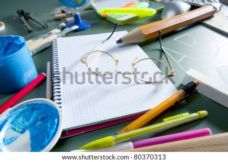 back to school still life on blackboard with teacher glasses pencil paint and several education stuff - stock photo
