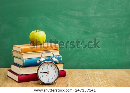 Back to school supplies over green  school blackboard - stock photo