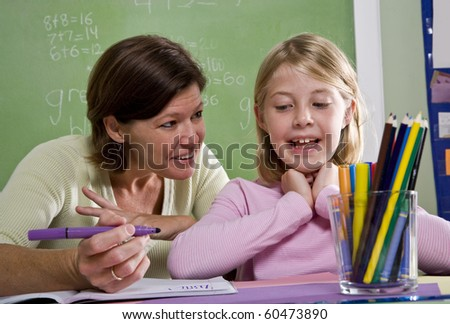 Back to school - teacher teaching 8 year old student in classroom - stock photo