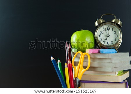 Back to school theme using school supplies and blackboard - stock photo