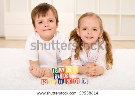 Back to school theme with kids playing on the floor - stock photo