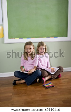 Back to school - two 8 year old girls doing homework together - stock photo