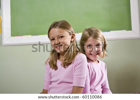 Back to school - two 8 year old girls in classroom - stock photo