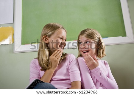 Back to school - two 8 year old girls in classroom by chalkboard