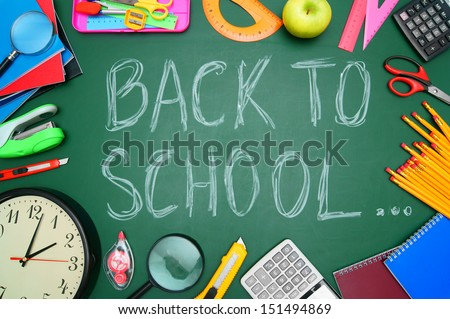 Back to school. Watch, a magnifier and other school subjects against a school board. - stock photo