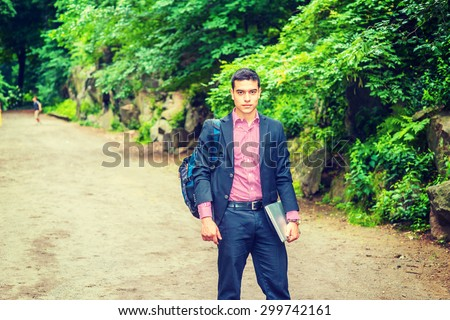 Back to School. Wearing black suit, red, white patterned undershirt, carrying shoulder bag, holding laptop computer, a young sexy college student standing in campus, looking forward. Instagram effect. - stock photo