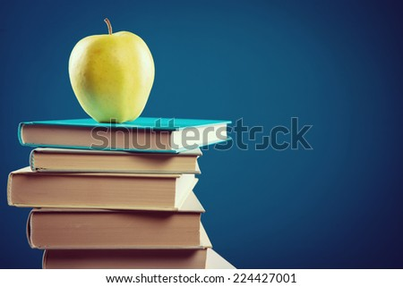Back to school with pile of books and yellow apple on blue background.