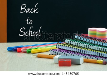 Back to school with school supplies on wooden desk - stock photo