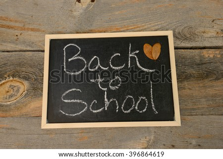 Back to School written in chalk on a chalkboard on a rustic background - stock photo