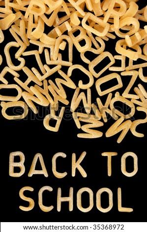 Back to school written in kids alphabet soup pasta. - stock photo