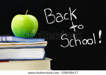 Back to School written on a blackboard with books and apple in front