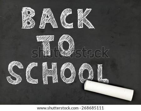Back to school written on blackboard with piece of chalk - stock photo