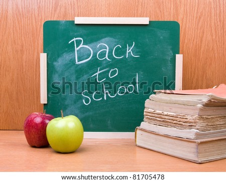 Back to school written on board with books and apples