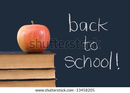 back to school written on chalkboard with apple, books - stock photo