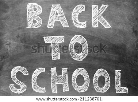 Back to school written on stained vintage blackboard - stock photo