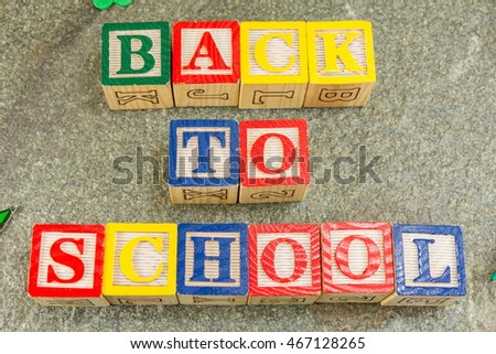 Back to school written with wooden letters on stone table