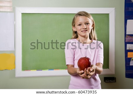 Back to school - 8 year old girl with apple for teacher - stock photo
