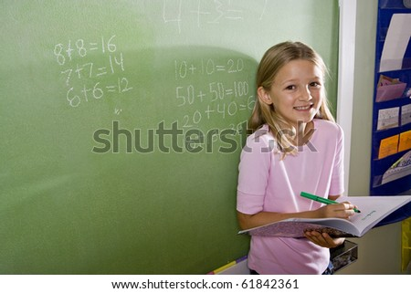 Back to school - 8 year old girls writing in notebook by blackboard in classroom, doing math