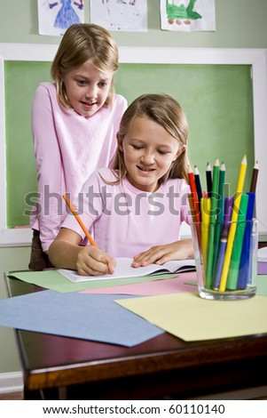Back to school - 8 year old girls writing in notebook in classroom