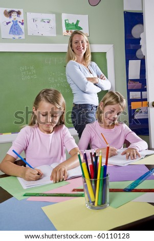 Back to school - 8 year old girls writing in notebooks in classroom with teacher watching - stock photo