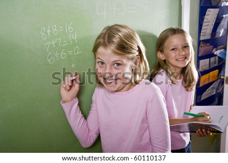 Back to school - 8 year old girls writing on blackboard in classroom, doing math - stock photo