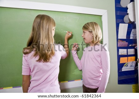 Back to school - 8 year old girls writing on blackboard in classroom, doing math