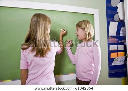 Back to school - 8 year old girls writing on blackboard in classroom, doing math - stock photo