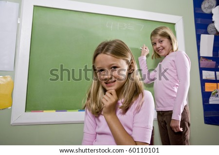 Back to school - 8 year old girls writing on blackboard in classroom, focus on foreground