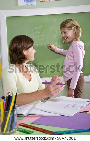 Back to school - 8 year old student and teacher by blackboard in classroom - stock photo