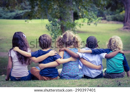 Back turned sitting children in the park on a sunny day - stock photo