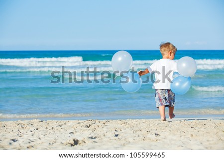 Back vie of cute little boy plays with ballons on the beach - stock photo