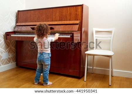 Back view. A child stands in front of the piano and plays a melody. Little pianist learning to play the piano. Baby, child ,kid and music concept.